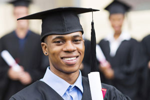 young man in a cap and gown smiling
